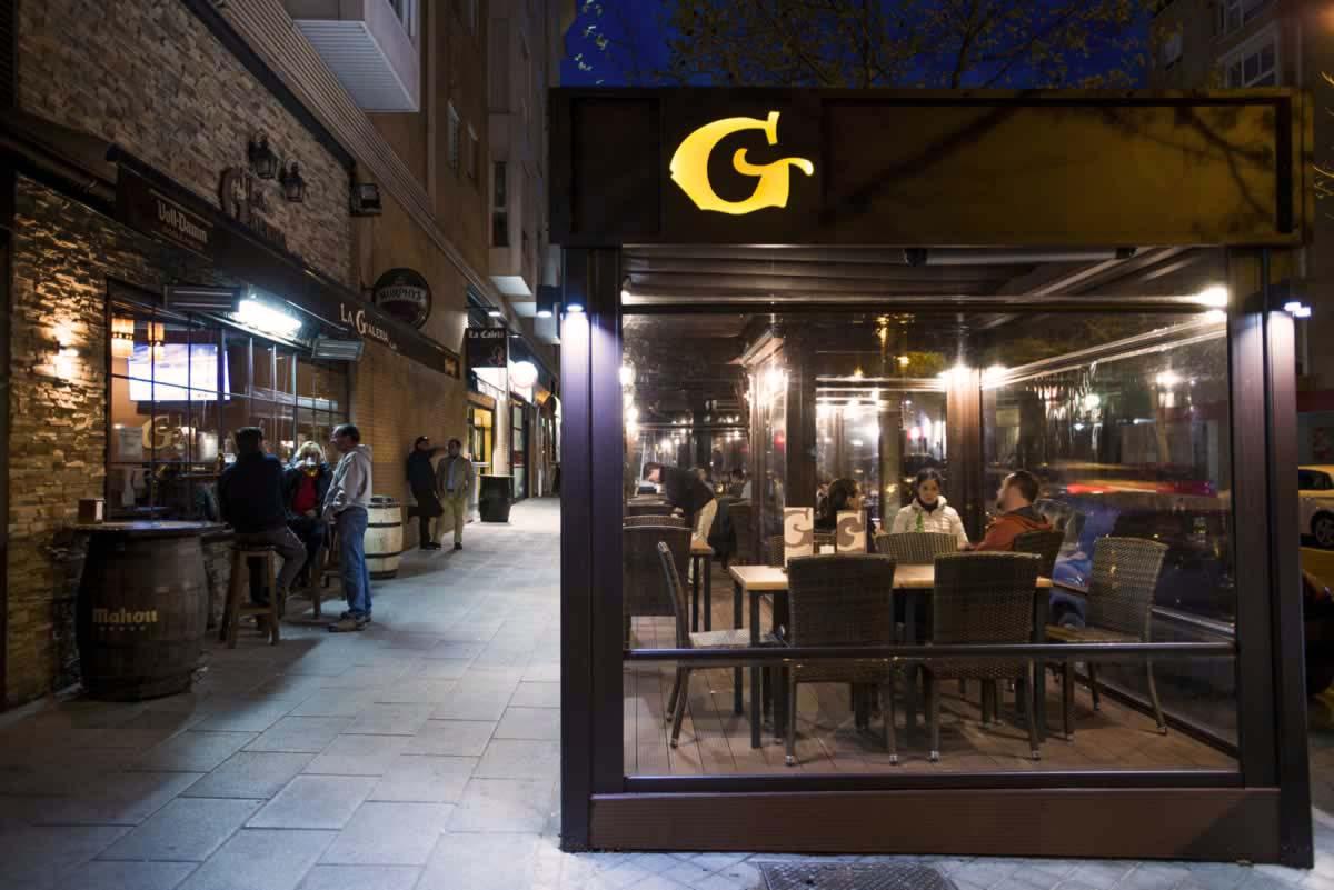 Obra realizada en terraza de cafetería, con pérgola, cortavientos transparente, tarima e iluminación