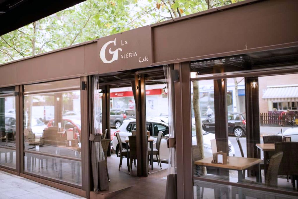 Obra realizada en terraza de cafetería, con pérgola, cortavientos transparente, y tarima, con bastidor publicitario calado