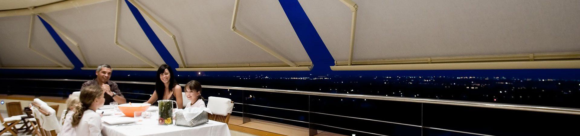 familia cenando con toldos cofre en balcon de fondo